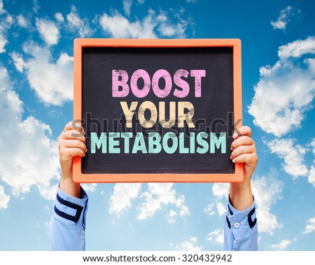 Hands holding Boost Your Metabolism written on chalkboard. - stock photo