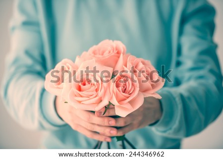 Hands holding bouquet of beautiful pink roses. Toned picture - stock photo