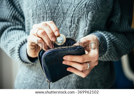 Hands holding british pound coin and small money pouch - stock photo