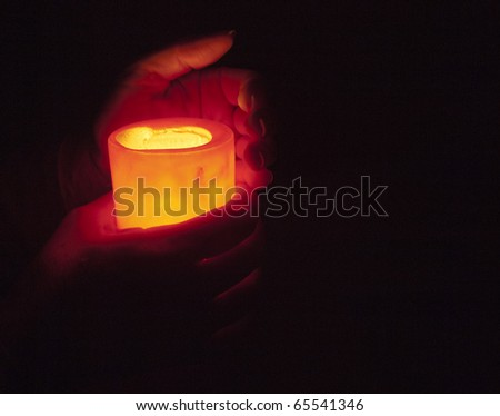 hands holding burning candle in the dark, room for type - stock photo