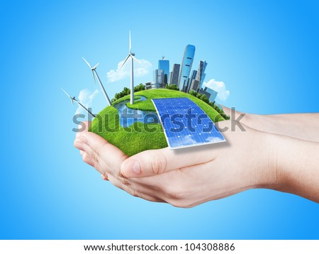 Hands holding clear green meadow with sun battery block, wind mill turbines and city skyscrapers. Concept for ecology, growing business, freshness, freedom. Green fields collection. - stock photo