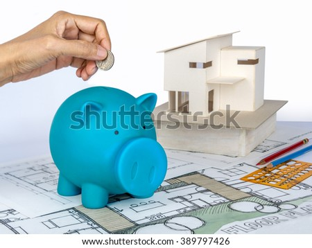 Hands holding coin over piggy bank with house model on top of blueprints / Housing industry mortgage and builder construction concept