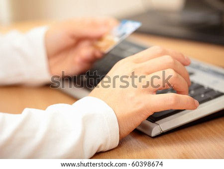 Hands holding credit card and keyboard. Shallow DOF - stock photo