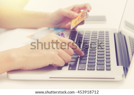 Hands holding credit card and using laptop. Online shopping card,credit card content,credit card background.
