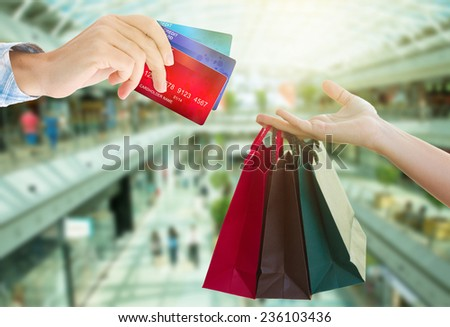 hands holding  credit cards and shopping bags in big shopping mall