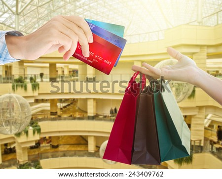 hands holding  credit cards and shopping bags in  shopping mall - stock photo
