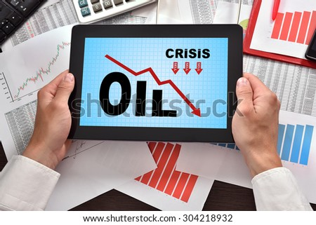 hands holding digital tablet with chart falling oil prices - stock photo