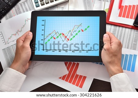hands holding digital tablet with chart on screen - stock photo