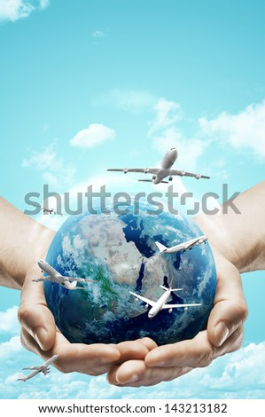 hands holding earth and airplane on sky background - stock photo