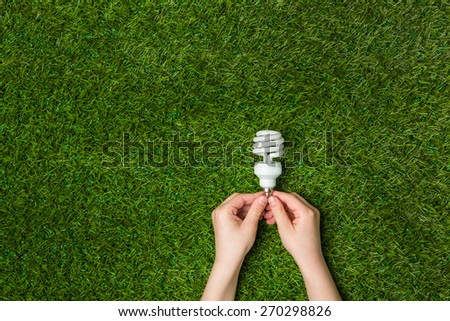 Hands holding  energy saving eco lamp over grass - stock photo