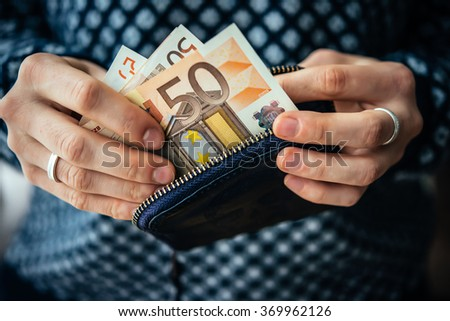Hands holding euro bills and small money pouch - stock photo