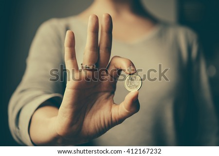 Hands holding european Euro coin. Toned image - stock photo