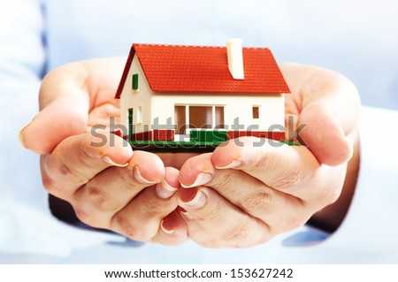 Hands holding Family house model. Real estate background. - stock photo
