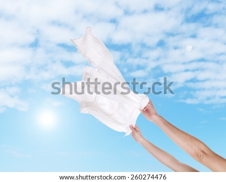 Hands holding flying shirt on sky background - stock photo