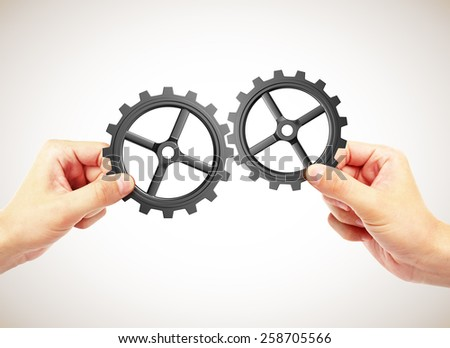 hands holding gears on gray background - stock photo