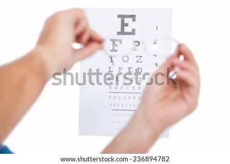 Hands holding glasses for eye test on white background