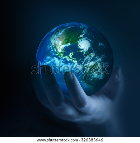hands holding glowing planet in the dark. Elements of this image furnished by NASA