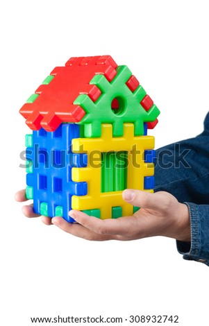 Hands holding house made of puzzle pieces on a white background - stock photo