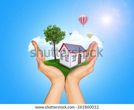 Hands holding house on green grass with tree, wind turbine and hot air balloons. Background clouds and blue sky - stock photo