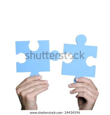 Hands holding large jigsaw puzzle pieces, isolated on white. - stock photo