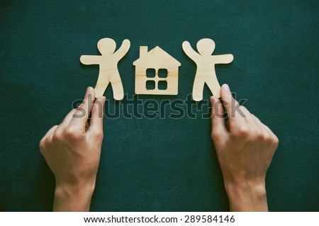 Hands holding little wooden men and house on blackboard background. Symbol of construction, sweet home concept - stock photo