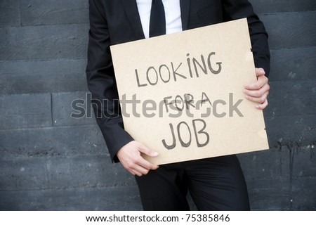 "Hands holding ""looking for a job"" sign - stock photo"