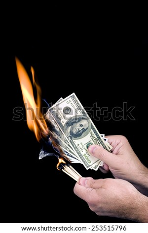 Hands Holding Matches And Burning False Hundreds/ Burning Cash - stock photo