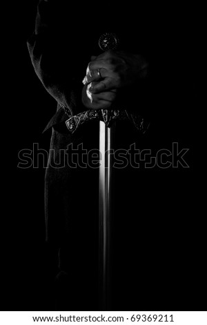 hands holding medieval sword on black background - stock photo