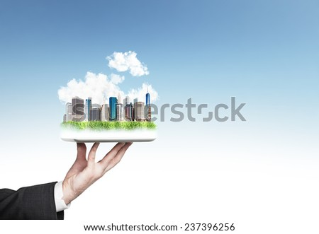 hands holding modern city on green grass hill - stock photo