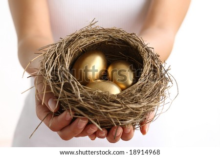 Hands holding nest with golden eggs - stock photo
