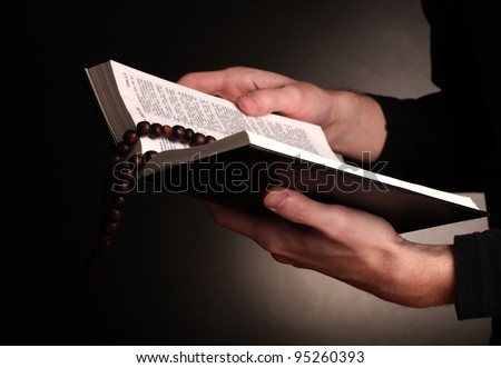 Hands holding open holy russian bible - stock photo