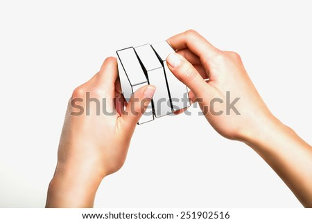 Hands holding or playing with white cube on white background - stock photo