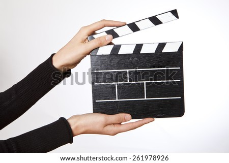 Hands holding out a clapper bord  on white background - stock photo