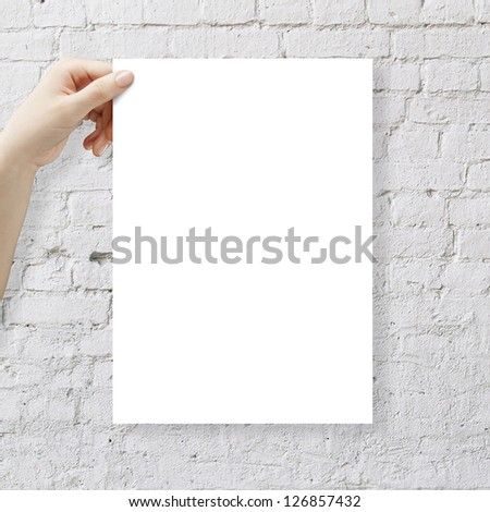 hands holding paper and brick wall - stock photo