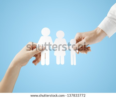 hands holding paper family  on a blue background - stock photo