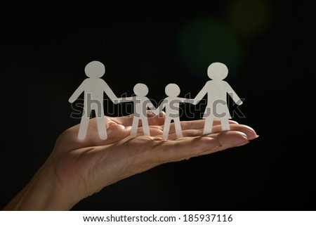 Hands holding paper family  on dark background - stock photo