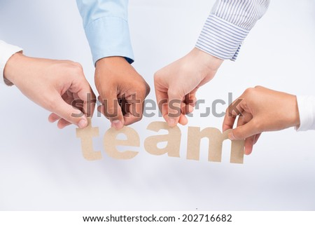 Hands holding paper letters that forming team - stock photo