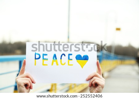 Hands holding paper with Peace of Ukraine - stock photo