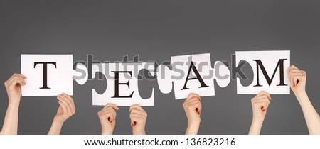 hands holding piecesof a puzzle building the word TEAM, gray background - stock photo