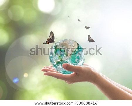 Hands holding planet + butterfly on blurred greenery color bokeh background of natural tree leaves facing sun flare: Saving world bio CSR environment concept: Elements of this image furnished by NASA  - stock photo