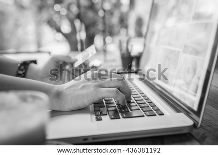 Hands holding plastic credit card and using laptop. working on laptop in a cafe. woman using laptop in home. using laptop internet. girl using laptop from thailand. hand using laptop in coffe shop - stock photo