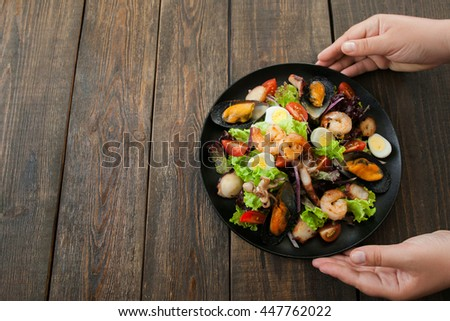 Hands holding plate with seafood mix salad on wooden background. Taking from wooden table plate with seafood salad hands. free space for commercials - stock photo