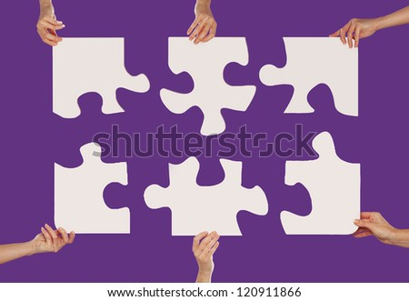 Hands holding puzzles business concept - stock photo