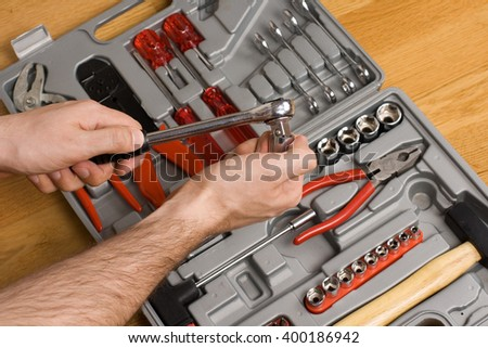 Hands holding ratchet and head over toolbox with different instruments  - stock photo