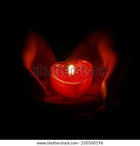 hands holding red candle in the shape of heart on black background - stock photo