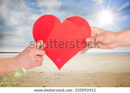 Hands holding red heart against serene beach landscape - stock photo