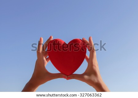 Hands holding red heart with clear blue sky and copy-space