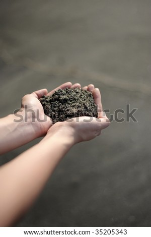Hands holding rich volcanic soil