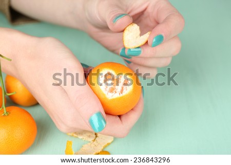 Hands holding ripe tangerine, close up - stock photo
