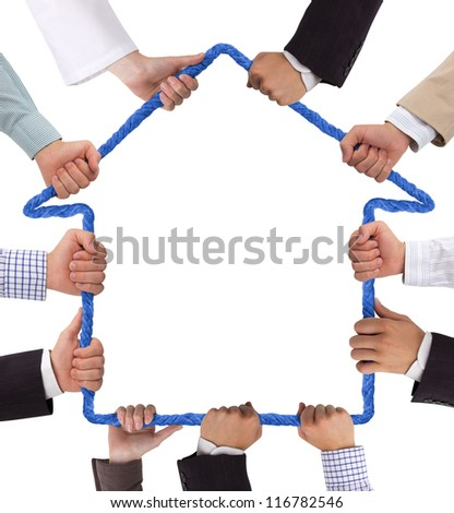 Hands holding rope forming house - stock photo